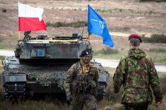 Ein Soldat aus Polen und ein Soldat aus den Niederlanden stehen sich vor einem Panzer, auf dem die Flaggen Polens und der NATO gehisst sind, gegenüber.
