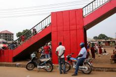 Zahlreiche afrikanische Frauen und Männder stehen und sitzen bei einem nach oben rechts aus dem Bild ragenden rot gestrichenen Treppenaufgang aus Beton. Vorn stehen zwei Krafträder; im Hintergrund ragt links ein Neubau, rechts improvisierte Stände auf.