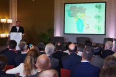 Links steht an einem Pult an ein Mann und spricht, rechts erscheint an der Wand eine Projektion des Kontinents Afrika mit eingeblendeten Staatsgebieten verschiedener Staaten; im Vordergrund sitzen zahlreiche Zuhörer und schauen zu dem Mann oder zur Wand.
