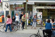 Vor einem Eckladengeschäft mit einer alten Straßenlaterne und Plasterstraße davor stehen und gehen zahlreiche Menschen verschiedener Herkunft und verschiedenen Alters, mehrere mit Fahrrädern; die gesamte Szene mutet durch Graffiti rauh und bunt an.