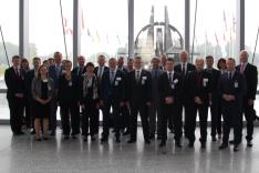Eine Gruppe geschäftlich gekleideter Menschen steht vor einer Plastik des NATO-Symbols und zahlreichen Flaggen von NATO-Mitgliedsstaaten.