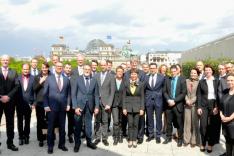 Eine Gruppe geschäftlich gekleideter Menschen steht auf einer Dachterrasse; im Hintergrund sind der Reichstag und das Brandenburger Tor in Berlin erkennbar.
