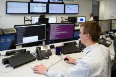 Ein Mann blickt an einem Schreibtisch sitzend auf sehr viele Bildschirme mit Zahlenreihen darauf; an der Wand im Hintergrund hängen weitere dieser Bildschirme, zum Teil mit anderem Inhalt wie zum Beispiel einem Nachrichtensender darauf.