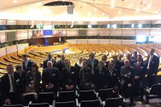 Zahlreiche geschäftlich gekleidete Menschen stehen erhöht vor den Rängen des Plenarsaals des Europäischen Parlaments.