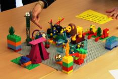 Eine Szenerie aus vielen bunten Lego-Plastikbausteinen bildet sicherheitspolitische Strategiebildungsprozesse ab.