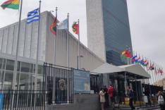 Hinter einer Reihe von Staatsflaggen ragt das Hauptgebäude der Vereinten Nationen in New York City auf.