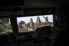 UN-Fahrzeuge fahren auf einer Straße. An der Seite befinden sich zerstörte Gebäude.