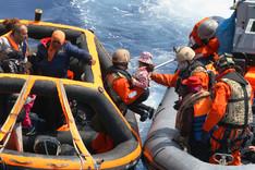 Aus einem Speedboat der Marine reichen deutsche Marinesoldaten ein Flüchtlingskind auf eine Rettungsinsel, die als Einstieg zu einem größeren Schiff dient.