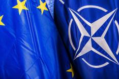 Die Flagge der EU und der NATO stehen dicht beieinander vor einem blauen Hintergrund.