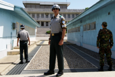 Uniformierte Soldaten mit Helmen und Sonnenbrillen stehen zwischen zwei hellblauen Barackengebäuden und blicken auf ein dahinter aufragendes großes Gebäude.