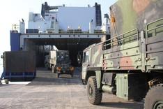 Lkws der Bundeswehr fahren auf ein Fährschiff.