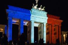 Nachtaufnahme des Brandenburger Tors, das in den französischen Nationalfarben Blau-Weiß-Rot angestrahlt wird.