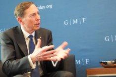 David Petraeus sitzt vor einer Pressewand des German Marshall Fund und spricht unterstützt von Gestik mit einem nicht im Bild befindlichen Gesprächspartner.