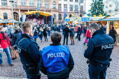 Drei Polizisten stehen bei Tag auf einem Weihnachtsmarkt während zahlreiche Passanten vorbeigehen.