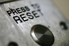 """Nahaufnahme eines Schaltknopfes auf einem Metallgehäuse, Beschriftung """"Press to Reset""""."""