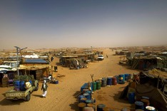 Ein provisorisches Flüchtlingslager erstreckt sich über ein Wüstenplateau bis zum Horizont.