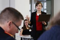 Zwei Frauen blicken zu einem General, der im Vordergrund sitzt; eine der Frauen sitzt; die andere steht, hält ein Notebook in der Hand und spricht gestikulierend.