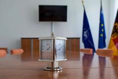 Auf einem Konferenztisch steht eine Uhr; im Hintergrund stehen drei Flaggen und ein Bildschirm hängt an einer weißen Wand.