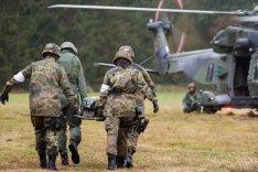 Soldatinnen und Soldaten tragen einen Kameraden zu einem Sanitätshubschrauber