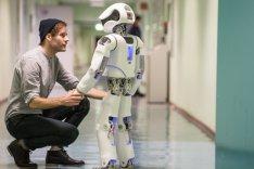 Ein junger Mann hält die Hand eines Roboters und schaut ihm in die Augen.