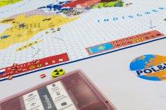 Auf einem Spielbrett mit einer Weltkarte liegen Spielkarten und -chips, rechts davon ist die Aufschrift Pol&IS zu lesen.