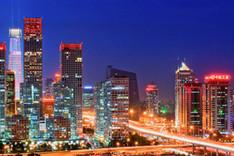 """Panoramabild von Pekings """"Central Business District"""" bei Nacht mit beleuchteten Bürohochhäusern und Außenwerbung"""