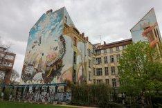 Das Bild zeigt eine bunt bemalte Hausfassade im Berliner Bezirk Neukölln