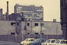 Straßenszene in Ostberlin in Mauernähe mit geparkten Wartburg- und Trabant-Pkws; Hinterlandmauer in der Schützenstraße, Ecke Charlottenstraße; im Hintergrund das Axel-Springer-Hochhaus in West-Berlin