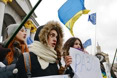 Demonstrierende Demonstantinnen auf einer Pro-Europa-Kundgebung in Kiew, 26. November 2013; im Hintergrund Flaggen der Ukranie und der Europäischen Union