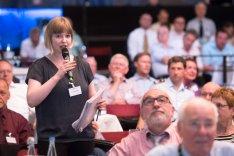 Eine junge Frau mit Unterlagen in der Hand spricht einen Diskussionsbeitrag in ein Mikrofon.
