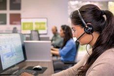 Profilbild einer Mitarbeiterin in einem Call Center mit Headset und PC