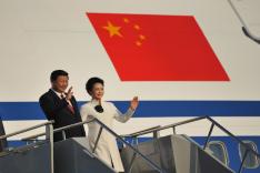Chinas Präsident Xi Jinping und seine Frau grüßen die Menschen vom Flugzeug aus. Im Hintergrund befindet sich eine chinesische Flagge.