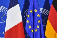 Vor einer blauen Pressewand des EU-Parlaments stehen die Flaggen Frankreichs, der EU und Deutschlands.