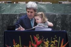 US-Außenminister John Kerry unterzeichnet 2016 mit seiner Enkelin auf dem Arm sitzend das Klimaabkommen von Paris.