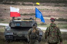 Ein Kampfpanzer mit NATO- und polnischer Flagge sowie zwei Soldaten auf einem militärischen Übungsgelände in Polen