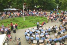 Auf einem ovalen Platz spielt ein uniformiertes Orchester und zahlreiche Menschen haben sich versammelt um zuzuhören.