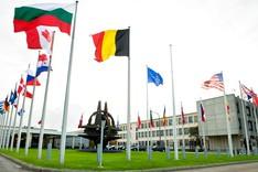 Die Flaggen der NATO-Mitgliedsstaaten und der NATO wehen auf dem zentralen Platz im NATO-Hauptquartier in Brüssel; in der Mitte des Platzes steht da NATO-Symbol als metallene Plastik.