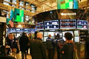 Börsensaal der New Yorker Börse mit vielen Bildschirmen, auf den Aktienkurse zu sehen sind.