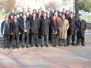 Gruppenbild mit 27 Damen und Herren in drei Reihen im Sonnenschein.