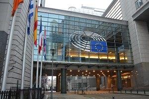 Ein großes Gebäude mit Fensterfront ist zu sehen, davor etliche Flaggen und die EU Flagge.