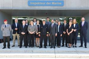 """Zahlreiche geschäftlich gekleidete Menschen, darunter drei Uniformträger, stehen vor einem Gebäude mit der Aufschrift """"Inspekteur der Marine""""."""