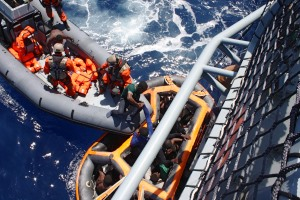 Ein Festrumpfschlauchboot mit Soldaten und eine Rettungsinsel voller Menschen liegen an der Bordwand eines Militärschiffs.
