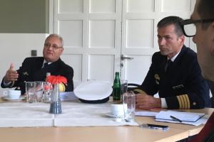 Zwei Männer in Marineoffizieruniformen sitzen an einem Tisch mit Tagungsunterlagen und sprechen zum Betrachter.