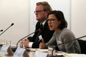 Eine junge Frau und ein junger Mann sitzen an einem Konferenztisch mit Mikrofonen; die Frau spricht.