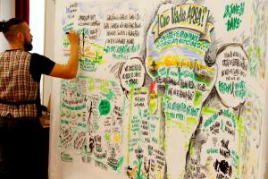 Ein Mann steht vor einem sehr großen vertikal aufgespannten Papierbogen und bringt mit einem Stift Text- und Grafikelemente darauf auf; in der Mitte des Bogens ist skizzenartig der afrikanische Kontinent erkennbar.