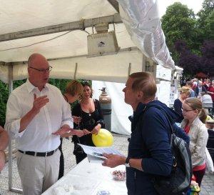 Christian Lipicki unterhält sich am Stand der BAKS auf dem Kunstfest mit einem Festbesucher.