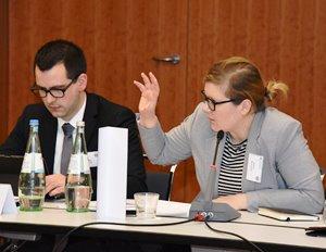 Links ein Mann, rechts eine Frau sitzen geschäftlich gekleidet an einem Tisch mit einem Mikrofon; die Frau spricht und gestikuliert.
