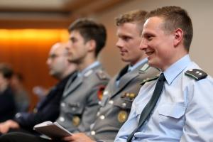 Drei Offiziere der Bundeswehr sitzen auf Stühlen.