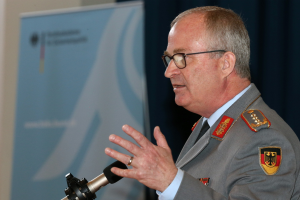 Ein uniformierter General der Bundeswehr spricht gestikulierend in ein Mikrofon.