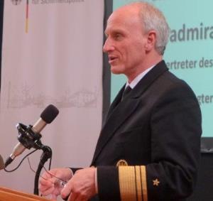 Ein Mann in einer Marineuniform steht an einem Rednerpult und spricht in ein Mikrofon.